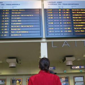 Mies katsoo juna-aikatauluja