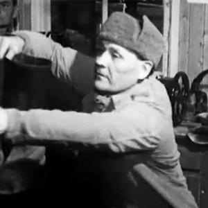 Työvelvollinen Juhani Norppa (Uljas Kandolin) ottaa saappaat näytelmässä Yhdeksän miehen saappaat.