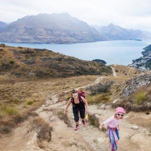 Satu Rämö kiipeää mäenrinnettä tyttärensä kanssa.