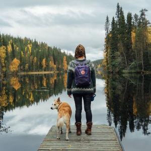 Nainen ja koira laiturilla syksyllä.