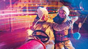 Kaksi tyttöä huvipuiston karusellissa pimeällä, pipot ja toppatakit päälllä