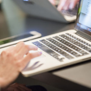 Tietokone on pöydällä, käsi käyttää hiirtä