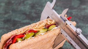 työntömitta täytetyn voileivän ympärillä