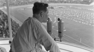 Toimittaja Martti Jukola selostamassa urheilutapahtumaa Helsingin Olympiastadionilla.