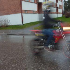 Mopedist i regnväder.