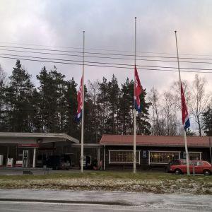 En bränslemack och tillhörande kafébyggnad, Teboil-flaggor i halvstång.