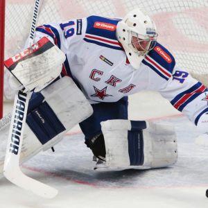 Ishockeymålvakt sträcker sig för att täcka puck.