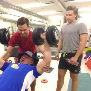 tre pojkar lyfter tyngder i gym