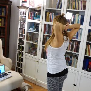 Nainen tekee seisoaltaan joogaliikettä joogaverkkopalvelun kautta.