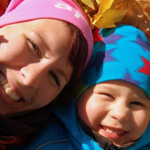 Äiti ja lapsi makaavat syksyllä lehtikasassa lähikuvassa.
