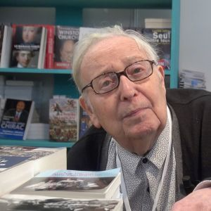 silmälasipäinen vanha mies katsoo kohti kirjakaupassa