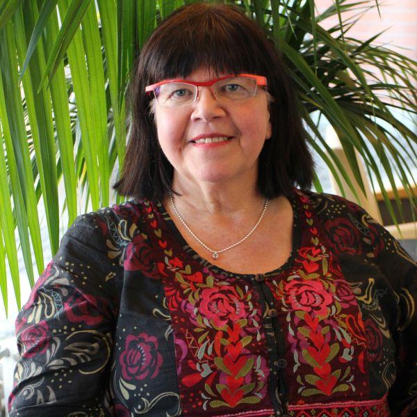 Tutkimusprofessori Merja Penttilä istuu huonekasvin edessä.