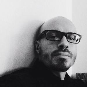 Silmälaipäinen mies mustsavalkoisessa kasvokuvassa.