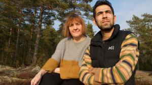 Asadullah Hasanzada och Pirkko Heiske sitter på ett berg i Sjundeå