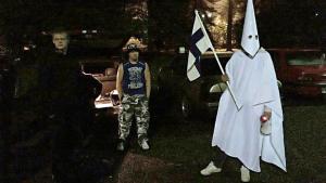Tre personer under en demonstration mot flyktingar. En person är klädd i Ku Klux Klan-kläder och bär en finsk flagga.