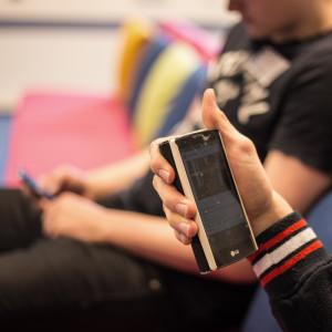 Ungdomar tittar på sina mobiltelefoner