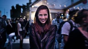 flickan står på festivalen och tittar in och ler i kameran