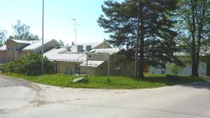 Lönnebergaskylt med den gamla delen av servicehemmet bakom sig.