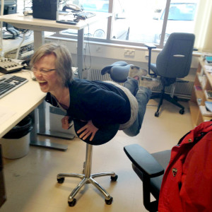 Pia Santonen halvligger över en kontorsstol och skrattar.