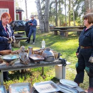 Keramiker Elina Sorainen tillsammans med kollegerna Pia Vuorinen och Ritva Turunen granskar resultatet av den senaste keramikugnsbränningen