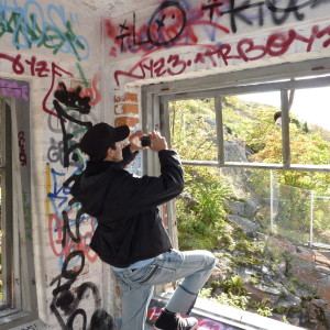 En kille som fotograferar klotter inne i ett övergivet hus.