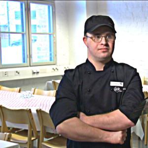 Manlig restauranganställd i i lunchmatsal.