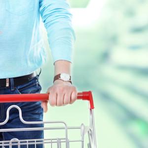 Mies työntää ostoskärryä älypuhelin kädessä