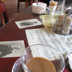 Keskeneräinen kahvikuppi kahvilan pöydällä, jolla nuotteja ja valokuvia.