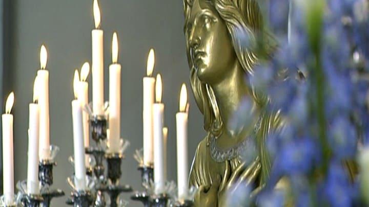 Levande ljus i en mångarmad ljusstake och en madonnastaty i bakgrunden