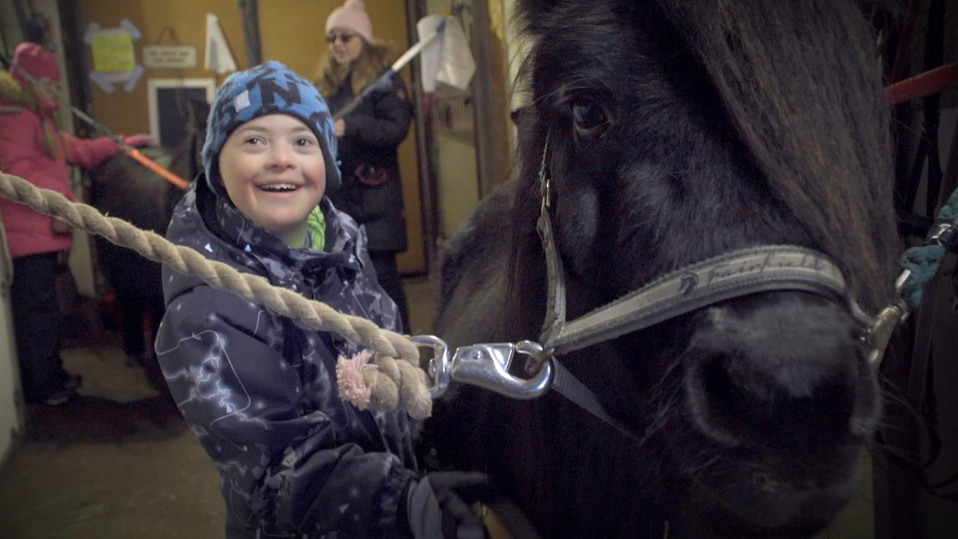 Tioåriga Lenni med downs syndrom står bredvid en häst