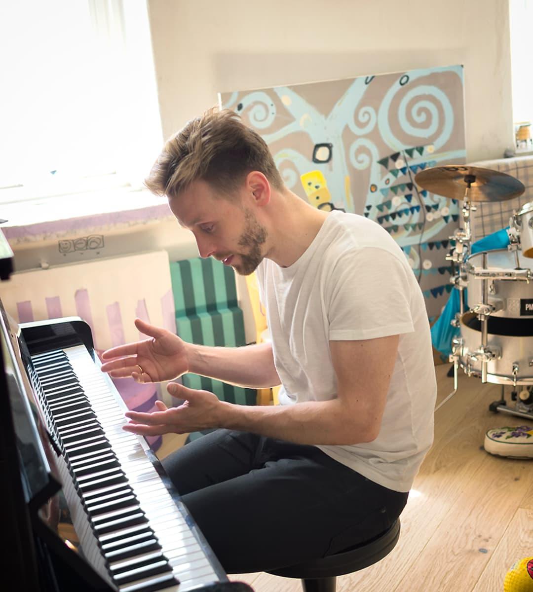 Reino Nordin kotonaan pianon ääressä. Taustalla näkyy öljyvärimaalaus ja rumpusetti.