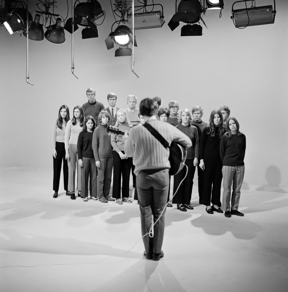 """Yleisradion televisio-ohjelma """"Popmessu. Pop-messu"""". Timo Ruottinen (kitara) ja 17-henkinen seurakuntanuorista koottu kuoro."""