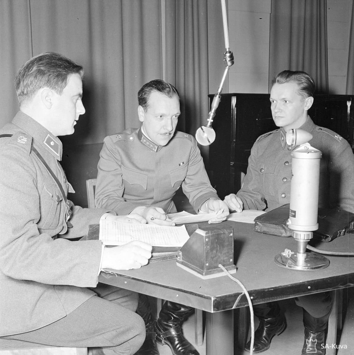 """Reservin vänrikki Kalle Lehmus (oik.), kapteeni Reino """"Palle Palmroth ja reservin vänrikki J.O. Tallqvist valmistautuvat radiolähetykseen lokakuussa 1939"""