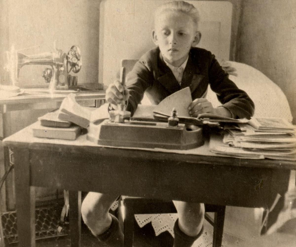 Mustavalkoinen kuva vakavasta nuoresta pojasta kirjoittamassa mustekynällä pulpetissa. Taustalla ompelukone pöydällä ja pitsipeittoinen vuode.