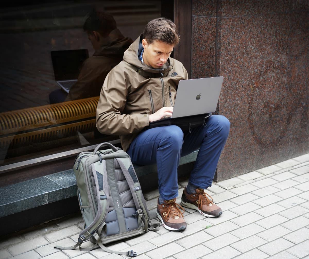 Roman Anin katsoo tietokonettaan kadulla.
