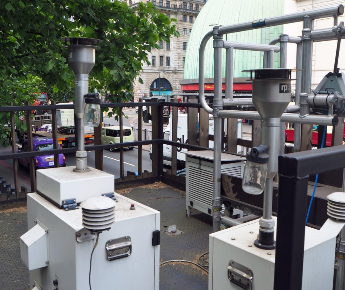 Laatikkomaisia laitteita, joissa on piiput. Taustalla Lontoon katuliikennettä.