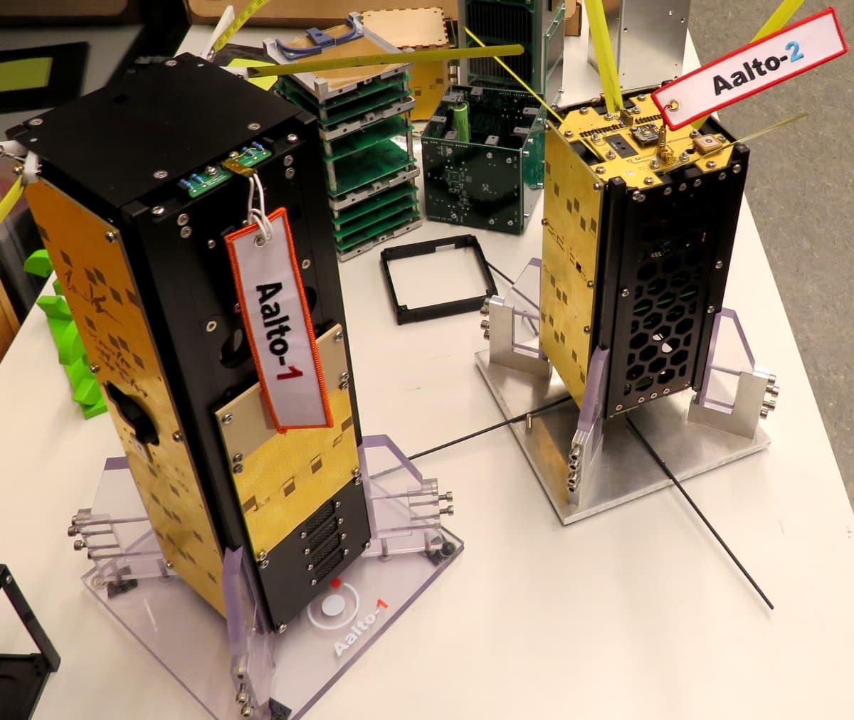 Kaksi maitopurkin kokoista ja muotoista laitetta, joissa on komponentteja.