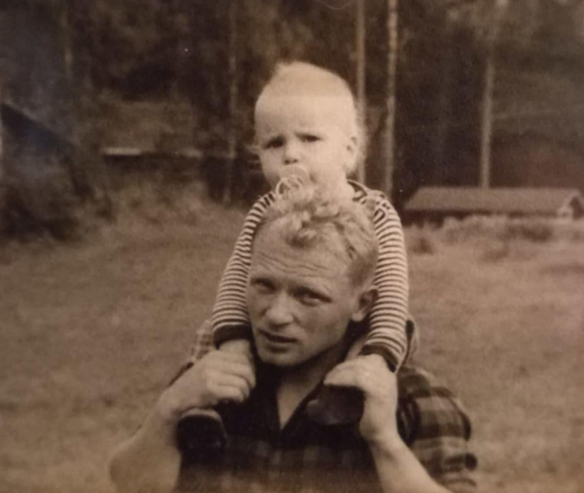 vanhassa mustavalkokuvassa on pieni poika tutti suussa isänsä harteilla.