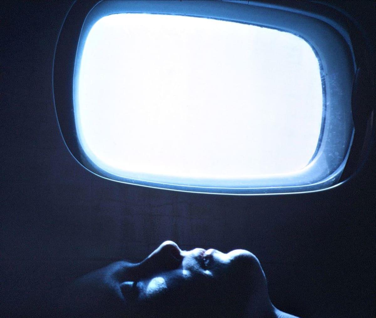 Mies nukkuu lentokoneessa.