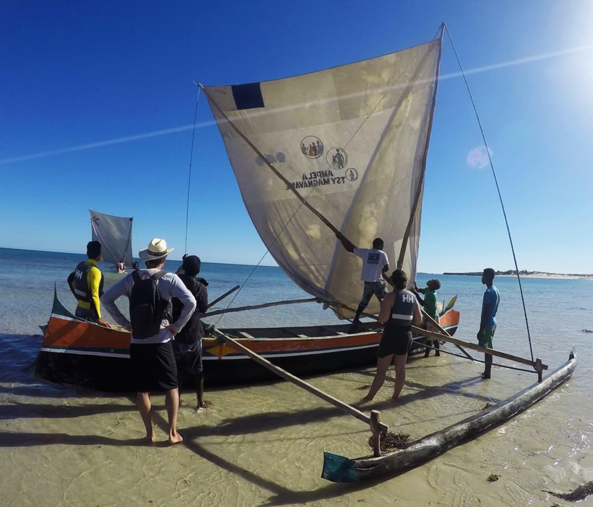 Ihmisiä lähdössä veneilemään madagaskarilaisella purjeveneellä.