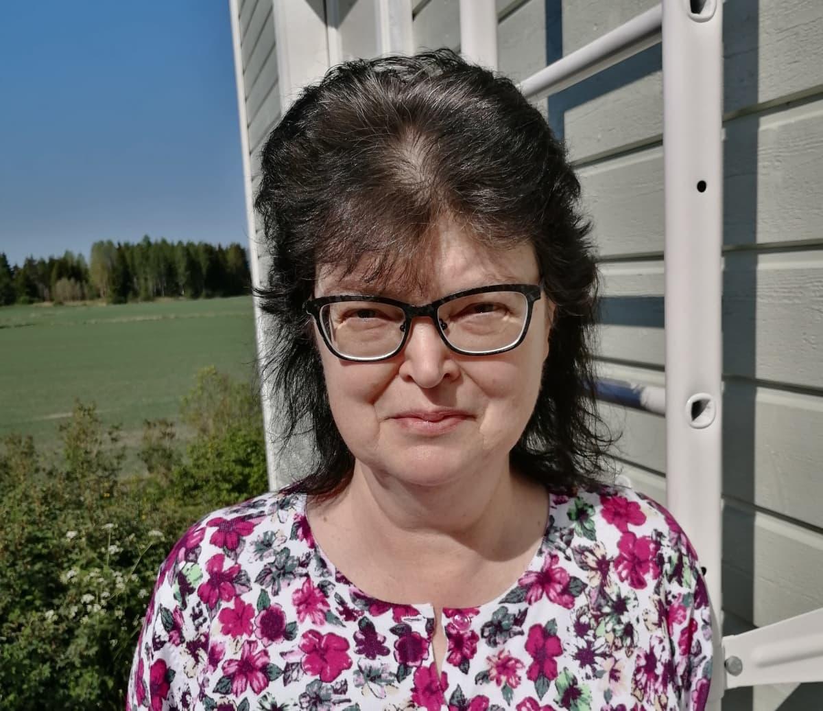 Rintakuva Marja Torkkelista talonsa vieressä.