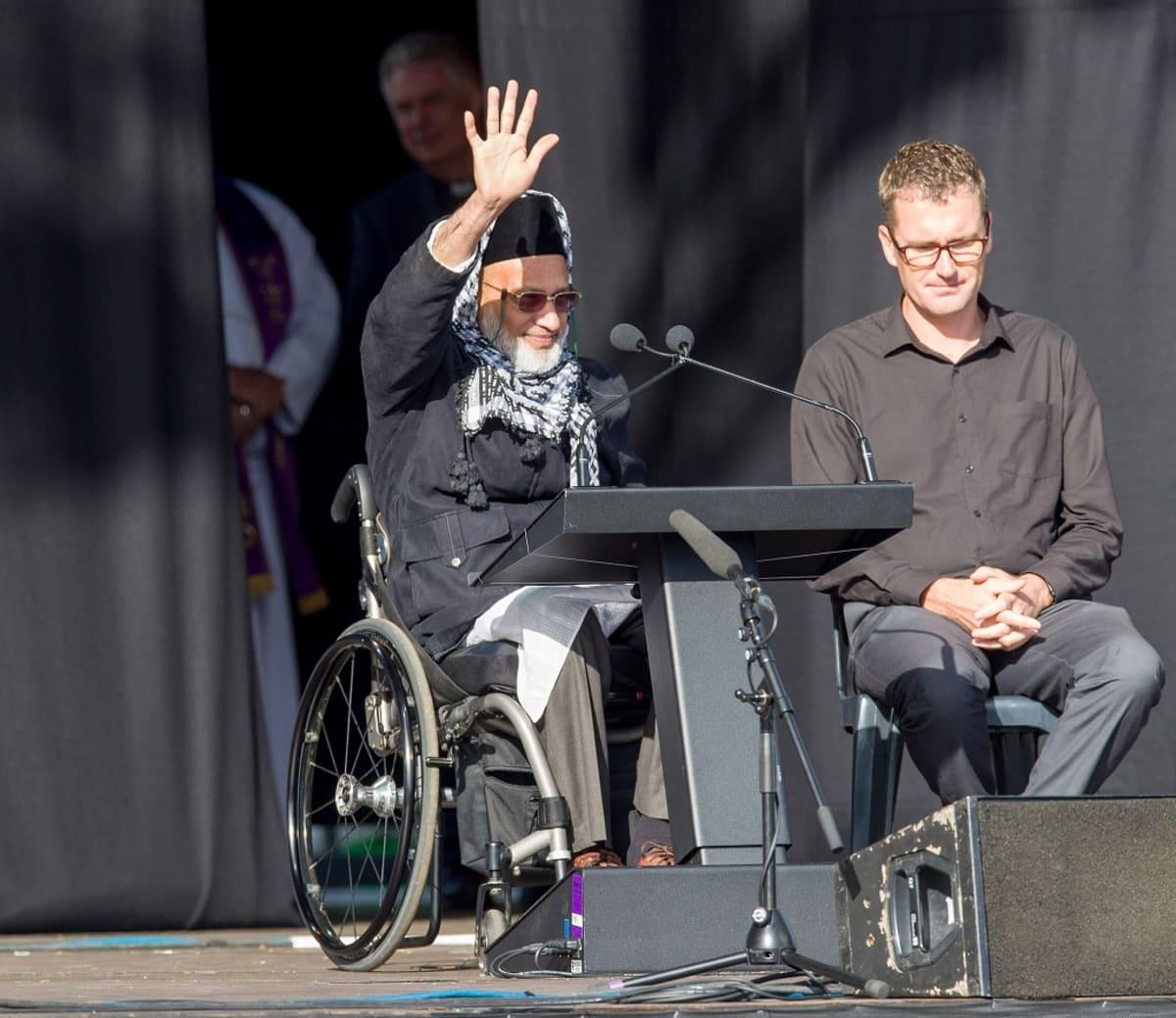 Pyörätuolissa istuva mies heiluttaa kättään puhujalavalla.