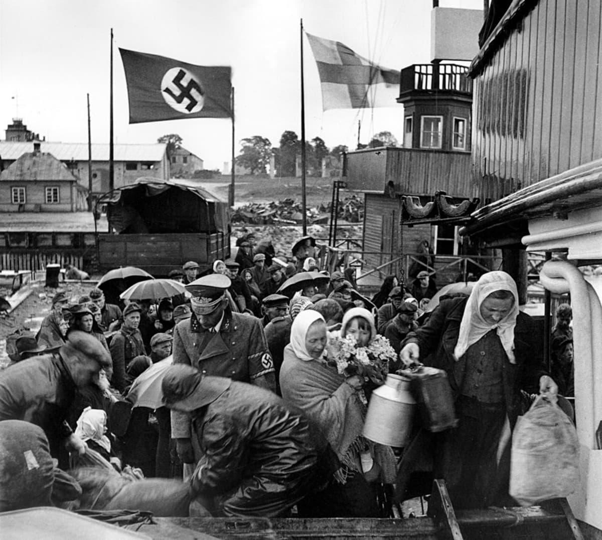 Inkeriläiset pakolaiset nousevat laivaan, saksalainen upseeri valvoo toimitusta.