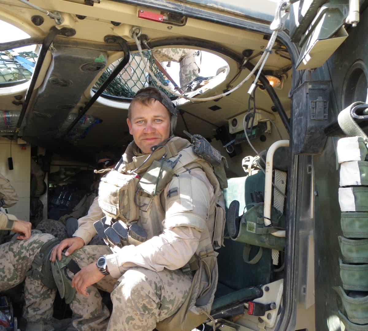 Maastopukuinen rauhanturvaaja istuu panssariajoneuvon takana paljain päin, katsoo kameraan ja hymyilee.