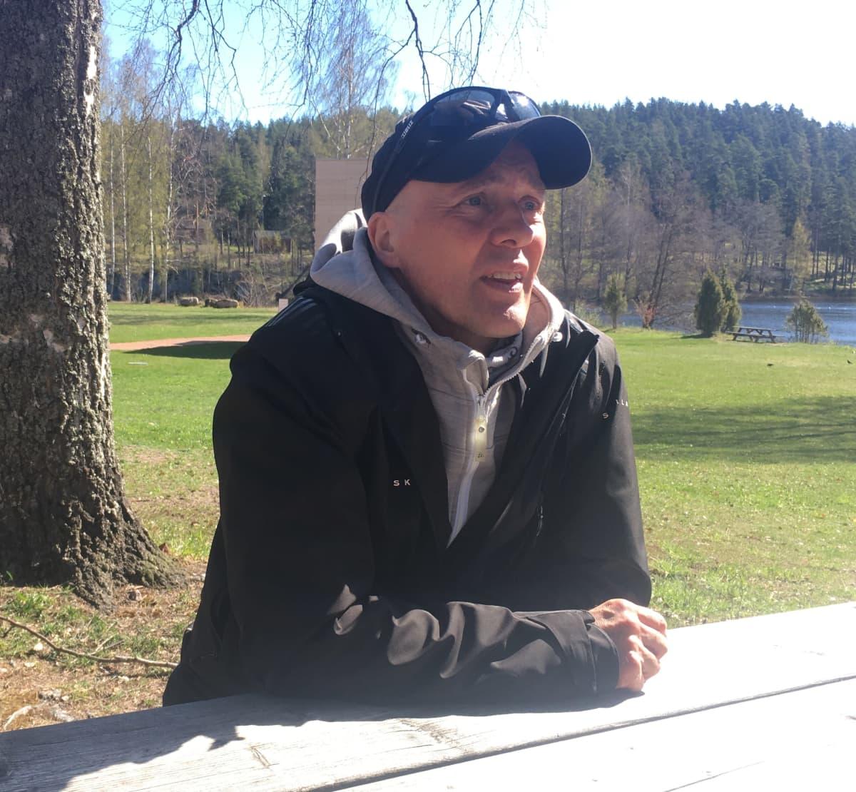 """Juha Seittonen """"Quuppa"""" istuu puupöydän ääressä ulkona"""