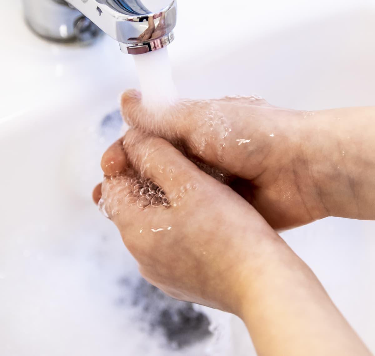 Kädet vesihanan alla.