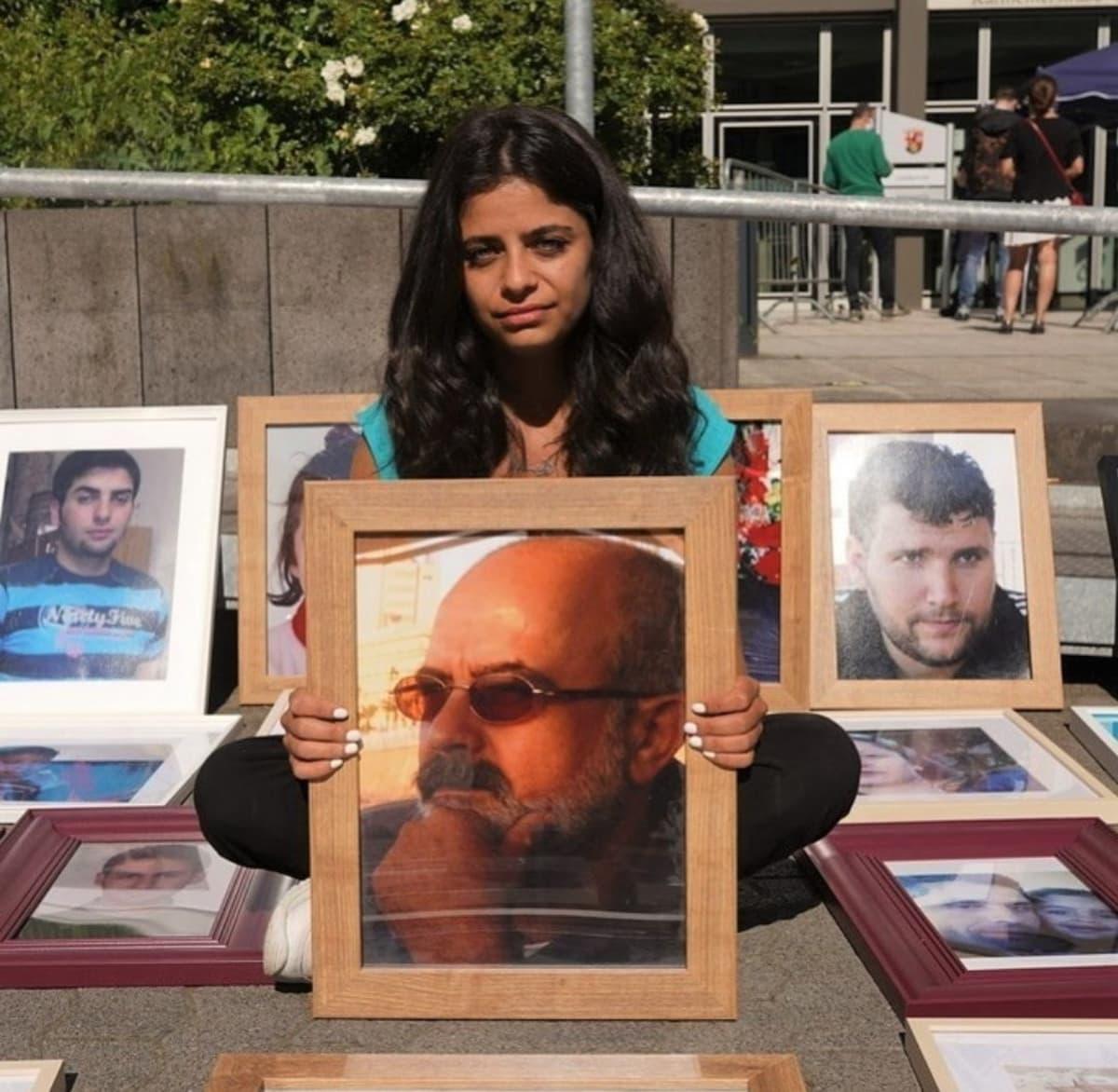 Syyrialaisnainen kädessään kuva kadonneesta isästään.