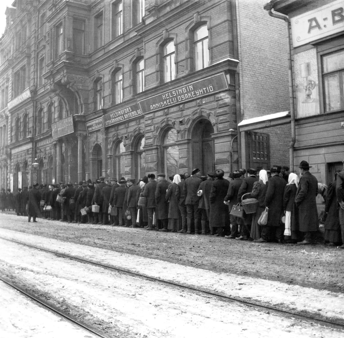 Historiallisessa kuvassa kansa jonottaa perunoita vuonna 1918.