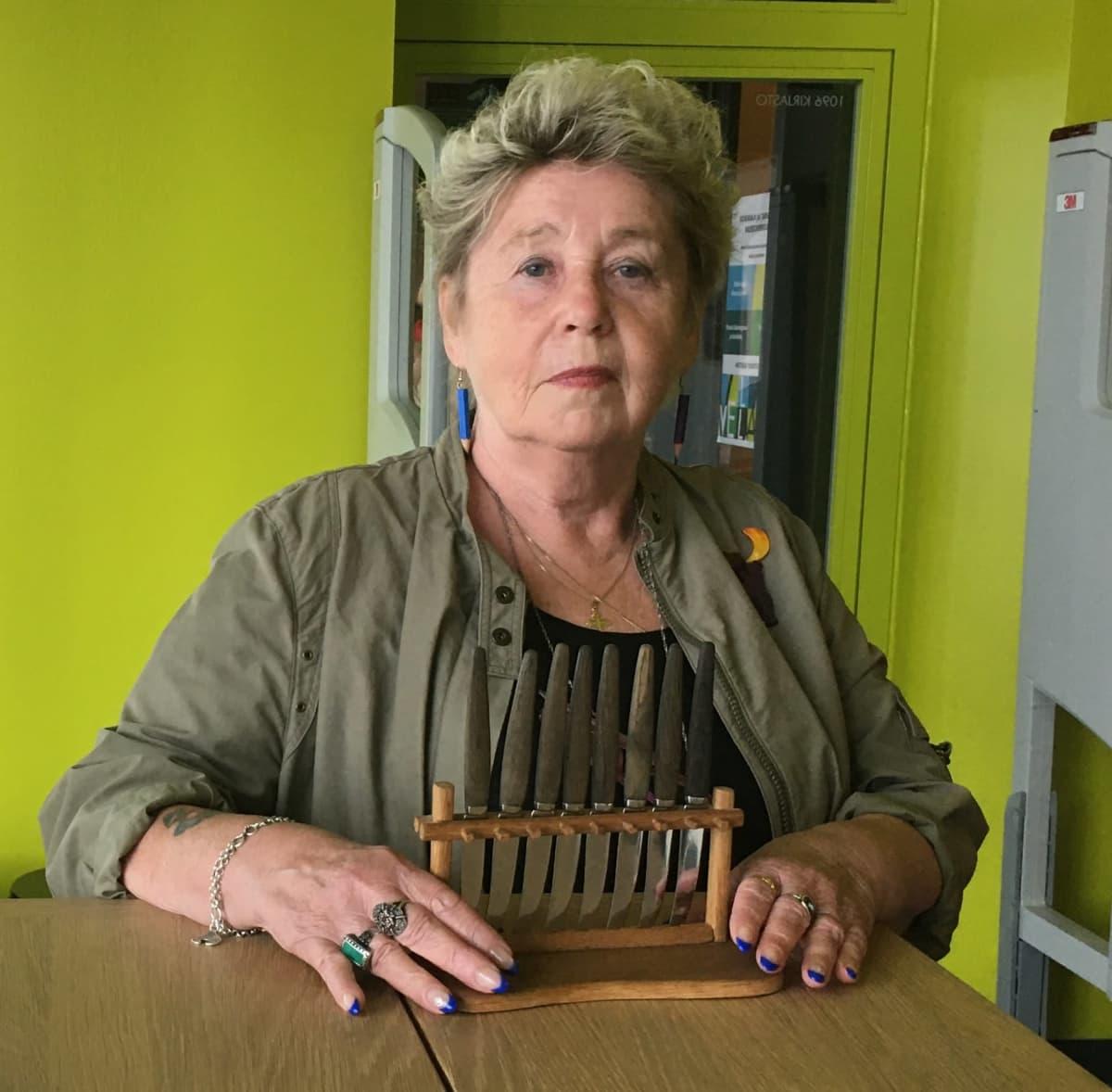 Nainen kuvassa veitsitelineen kanssa.