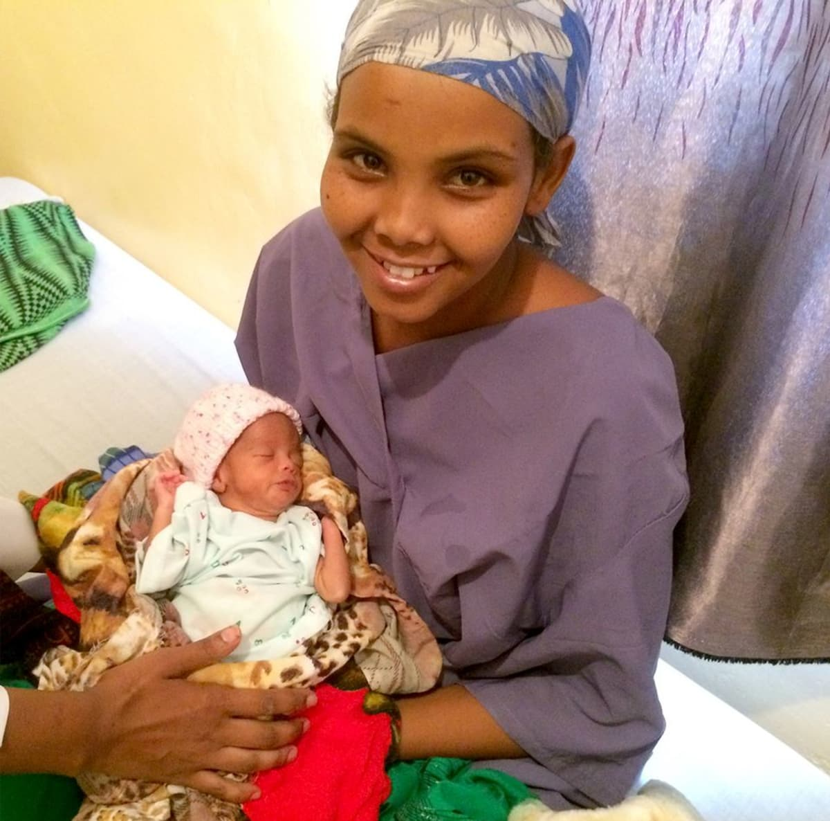 somaliopiskelija hymyilee vastasyntynyt vauva sylissään.